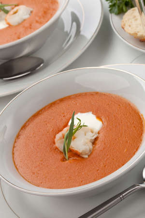 tarragon: Two bowls of lobster bisque garnished with slice of lobster tail, cream, and fresh tarragon  Fresh backed Italian bread and white wine