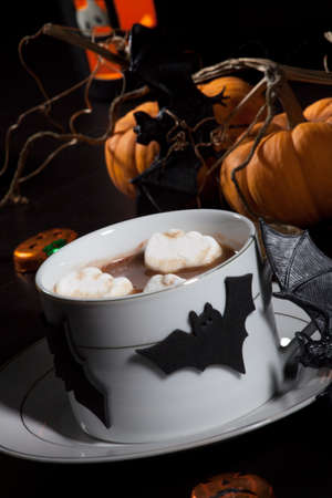 Cup of hot chocolate with ghost marshmallow, surrounded with pumpkins, candles, and Halloween decoration  Halloween drinks series  photo