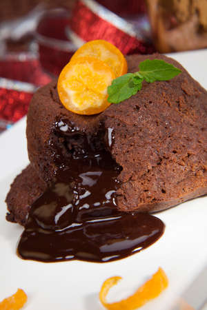 Delicious dark chocolate lava cake dessert served with fresh cumquat and mint  Surrounded by Christmas ornaments