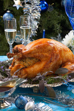 christmas turkey: Roasted turkey garnished with herbs on blue Christmas decorations, and champagne   Stock Photo