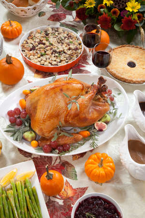 thanksgiving dinner: Roasted turkey on a server tray garnished with fresh figs, grape, kumquat, and herbs on fall harvest table  Red wine, side dishes, pie, and gravy  Decoraded with mini pumpkins, candels, and flowers