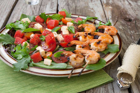 prawn skewers: Plate of a grilled shrimp salad with feta cheese, tomatoes, and watermelon in a rustic setting