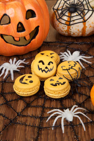 Closeup of Halloween decor with French pumpkin macaroons and assorted pumpkins. photo