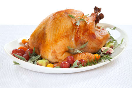 Roasted turkey on tray garnished with red grapes, figs, kumquat, and herbs over white background photo