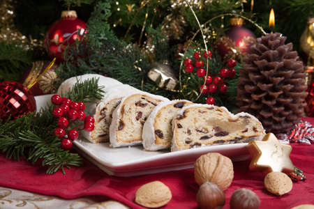 Traditional German Christmas cake - Cranberry Stollen, Christmas tree, ornaments, and candles.