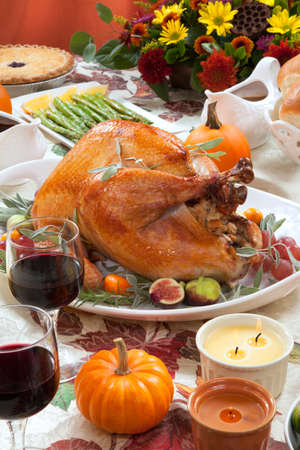 roasted turkey: Roasted turkey on a server tray garnished with fresh figs, grape, kumquat, and herbs on fall harvest table. Red wine, side dishes, pie, and gravy. Decoraded with mini pumpkins, candels, and flowers.