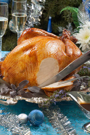 Carving roasted turkey garnished with herbs on blue Christmas decorations, and champagne. Christmas tree as background.