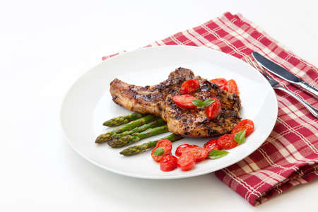 pork chop: Grilled pork chops and asparagus. Served with fried grape tomatoes salad and pesto sauce.
