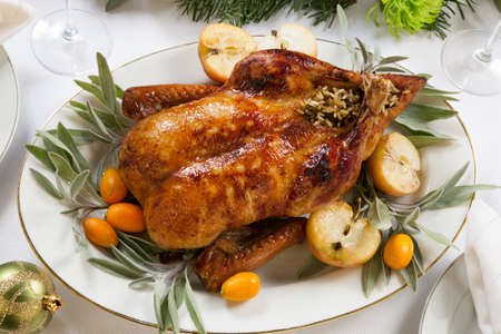 feast: Citrus glazed roasted duck stuffed with rice, garnished with apples, kumquats, and sage.