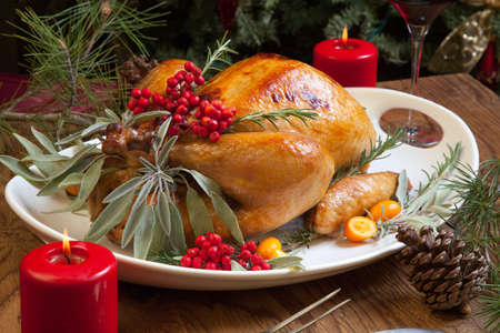 traditional: Roasted turkey garnished with sage, rosemary, and red berries in a tray prepared for Christmas dinner. Holiday table, candles and Christmas tree with ornaments. Stock Photo