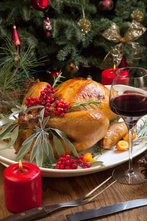 christmas turkey: Roasted turkey garnished with sage, rosemary, and red berries in a tray prepared for Christmas dinner. Holiday table, candles and Christmas tree with ornaments. Stock Photo