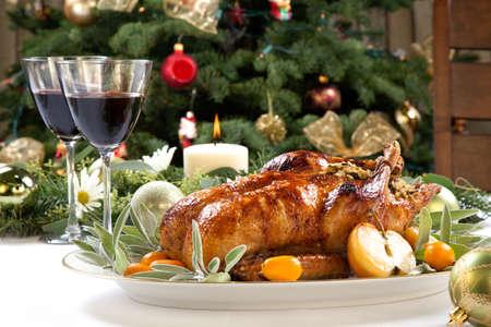 comida de navidad: Citrus esmaltado pato asado relleno con arroz, adornado con manzanas, naranjas chinas, y la salvia. Navidad decorado ajuste. Foto de archivo