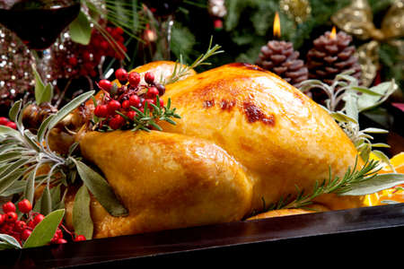 Roasted turkey garnished with sage, rosemary, and red berries in a tray prepared for Christmas dinner. Holiday table, candles and Christmas tree with ornaments. Standard-Bild