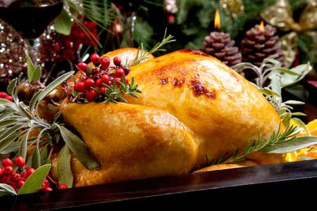 turquia: Pavo asado con guarnici�n de salvia, romero y bayas rojas en una bandeja preparada para la cena de Navidad. Alquiler de tabla, las velas y el �rbol de Navidad con adornos. Foto de archivo