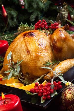 högtider: Rostad kalkon garnerad med salvia, rosmarin, och röda bär i ett fack förberedd för julmiddagen. Semesterbord, ljus och julgran med smycken.