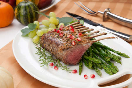 rack of lamb: Herb crusted rack of lamb garnished with asparagus, green grapes, and pomegranates. Mini pumpkins and fresh fruits.