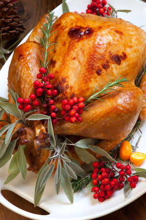Roasted turkey garnished with sage, rosemary, and red berries in a tray prepared for Christmas dinner. Holiday table, candles and Christmas tree with ornaments. Stockfoto