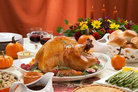 pavo: Pavo asado en una bandeja servidor adornado con higos frescos, uva, naranja china y hierbas en la mesa de la cosecha de otoño. El vino tinto, platos, pastel, y salsa. Decoraded con mini calabazas, velas y flores.