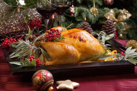 turquia: Pavo asado con guarnici�n de salvia, romero, y bayas rojas en una bandeja preparada para la cena de Navidad. Cuadro de vacaciones, las velas y el �rbol de Navidad con adornos.