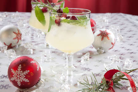 cranberry: Close-up of white cranberry spritzer cocktail on holiday table with Christmas ornaments. Holiday cocktails series.
