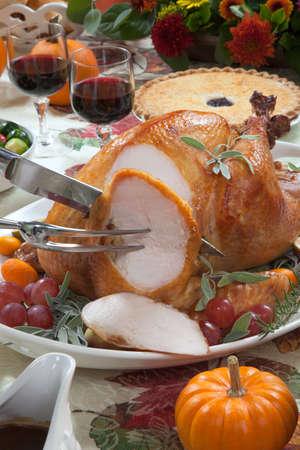contorni: Carving tacchino arrosto su un vassoio di server guarnito con fichi freschi, uva, kumquat, e le erbe sul tavolo la raccolta di caduta. Vino rosso, contorni, torta, e sugo. Decoraded con mini zucche, candele e fiori.