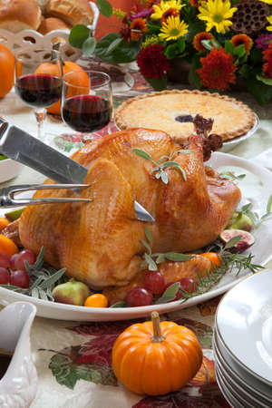 Carving roasted turkey on a server tray garnished with fresh figs, grape, kumquat, and herbs on fall harvest table. Red wine, side dishes, pie, and gravy. Decoraded with mini pumpkins, candels, and flowers. photo