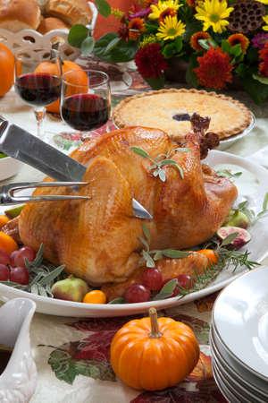 contorni: Carving tacchino arrosto su un vassoio di server guarnito con fichi freschi, uva, kumquat, ed erbe sul tavolo raccolta di caduta. Vino rosso, contorni, torta, e sugo. Decoraded con mini zucche, candele e fiori.