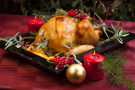 Roasted turkey garnished with sage, rosemary, and red berries in a wooden tray on Christmas decorated table. Candles and Christmas tree with ornaments.
