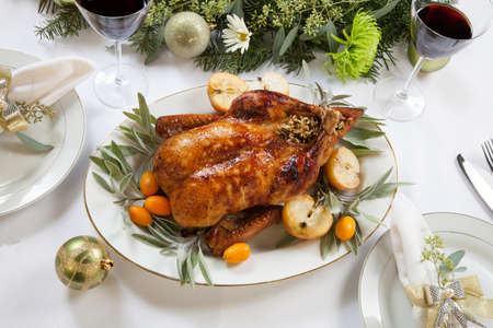 feast: Citrus glazed roasted duck stuffed with rice, garnished with apples, kumquats, and sage. Christmas decorated setting.