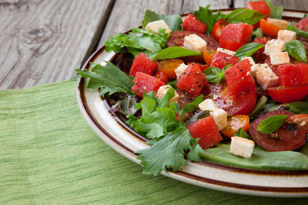 feta: Plate of a salad with feta cheese, tomatoes, and watermelon in a rustic setting.