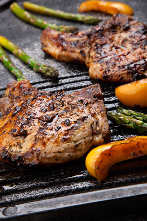 grilled pork: Juicy pork chops are grilled on griddle with asparagus and bell pepper. Backyard grilling for summer picnic.