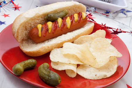 hot dogs: Hot dog, chips, and pickled cucumbers. Angel food fruit cakes and muffins on 4th of July in patriotic theme in background. Stock Photo