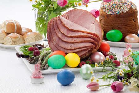 Hela bakade honung skivad skinka med färsk hallon, sparris, färgade Ester ägg, påsktårta, och tvär bullar. Vårblommor. Stockfoto