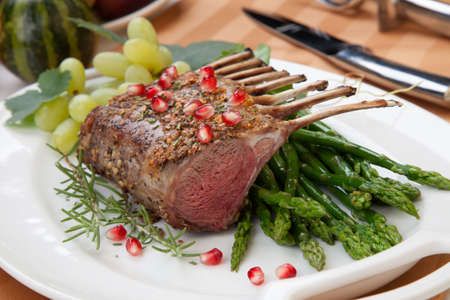 crusted: Herb crusted rack of lamb garnished with asparagus, green grapes, and pomegranates. Mini pumpkins and fresh fruits.