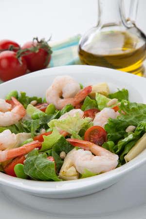 romaine: Plate of Italian shrimp salad with shrimp, tomatoes, artishocke hearts, Romane lettuce leaves, fava beans, and pine nuts. Olive oil.