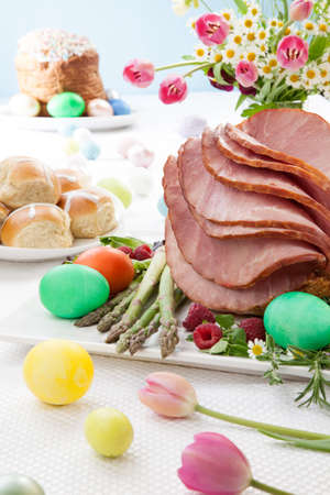 Whole baked honey sliced ham with fresh raspberry, asparagus, dyed Ester eggs, Easter cake, and cross buns. Spring flowers.