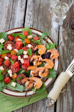 prawn skewers: Plate of a grilled shrimp salad with feta cheese, tomatoes, and watermelon in a rustic setting.
