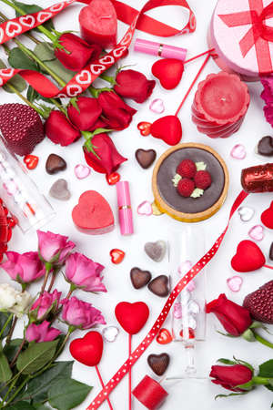 Assortiment of different Valentine Day gifts, candies, red roses, cosmetics, candles, and bottle of Champagne. Stock Photo