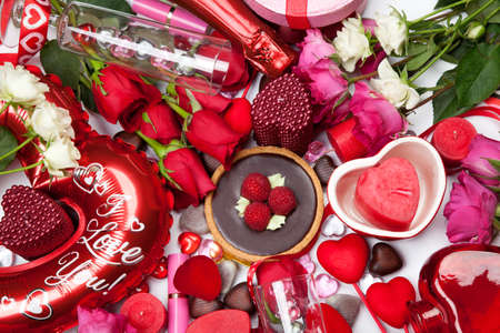 Close up of Valentine Day assortiment of different gifts, candies, red roses, cosmetics, candles, and bottle of Champagne.