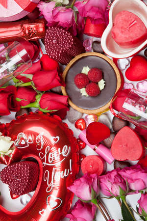 Close up of Valentine Day assortiment of different gifts, candies, red roses, cosmetics, candles, and bottle of Champagne. photo