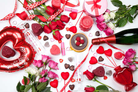 Assortiment of different Valentine Day gifts, candies, red roses, cosmetics, candles, and bottle of Champagne. photo