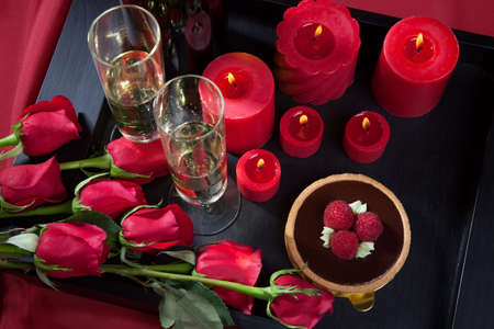 Glasses of champagne and candles: Celebration tray for Valentines Day - Champagne, chocolate raspberry cake, candles, and red roses.