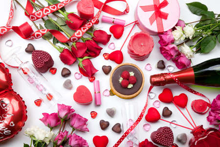 champagne truffles chocolate: Assortiment of different Valentine Day gifts, candies, red roses, cosmetics, candles, and bottle of Champagne. Stock Photo