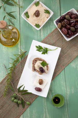 sandwitch: Appetizer plate with whole grain bread with hummus, feta cheese, olives, and parsley.