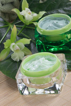ointment: Closeup gorgeous blooming green colored Cattleyas orchid flowers and jars of cosmetics cream. Stock Photo