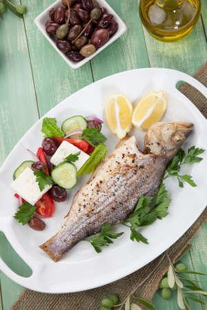 sea bass: Mediterranean style organic roasted whole sea bass, garnished with Greek salad. Stock Photo