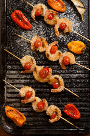 Grilled Parmesan crust shrimp with chery tomatoes on the grill with grilled mini bell peppers.
