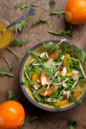 mandarin oranges: Closeup of a plate of arugula salad with mandarins oranges beans sprouts and sliced almonds served with mandarin vinaigrette for healthy lunch.