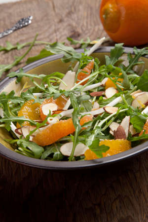 Closeup of a plate of arugula salad with mandarins oranges beans sprouts and sliced almonds served with mandarin vinaigrette for healthy lunch.