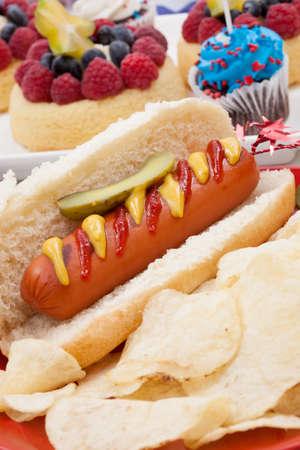 angel de la independencia: Fichas de perros calientes y pepinos en vinagre. �ngel pasteles fruta y panecillos en 4 de julio en tema patri�tico en fondo. Foto de archivo